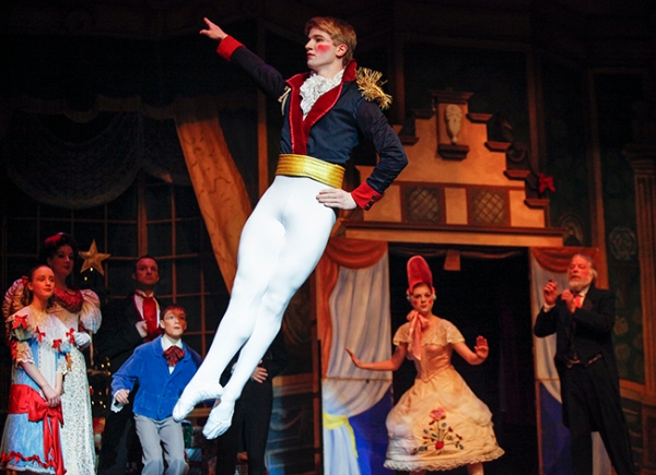 Guests look on during the first-act party scene as Ian Zeisel dances the role of soldier doll.