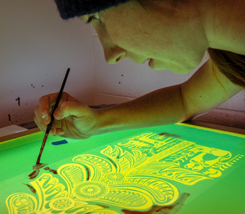 Klara Maisch fills in holes on screen before screen printing.