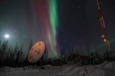Earth's originally satellite the moon, a satellite receiving dish and radio tower, all visible on top of Ski Boot Hill as northern lights streak overhead.
