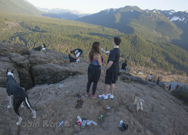 Hikers enjoy the view, share photos, and make a mess and dogs roam at Rattlesnake Ridge.