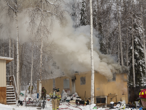 Smoke spews out of a mobile home off Rainbow Drive, north of Fairbanks.