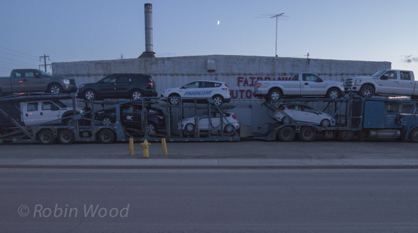 Car transport parked with crescent moon above. May 16, 12:02 a.m.
