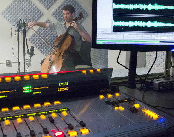 Recording levels, wavelengths and board lights in the foreground, cello playing in the background.