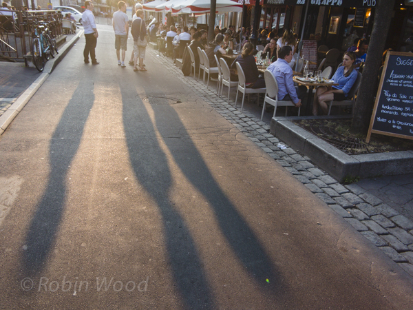 Pedestrians cast long shadows walking by packed cafes.