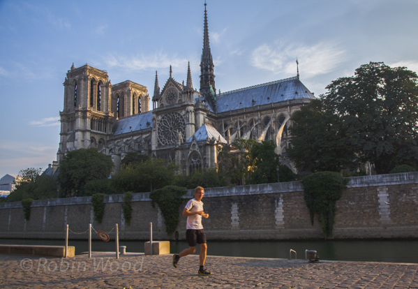 A jogger makes his way along the Seine River with Notre-Dame Cathedral in the background, July 8, 2013.