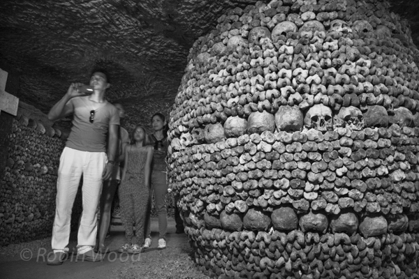 A family with surprisingly young children work their way through the catacombs.