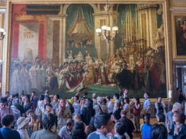 "Replica of ""The Crowning of Empress Josephine by Napoleon in Notre-Dame of Paris on 2 December 1804."" Throngs of tourists blur make it difficult to tell where the life-sized painting begins and ends."