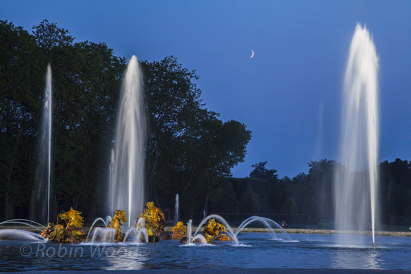 A crescent moon begins to rise over the fountain.