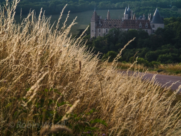 The 13th-centure Château de la Rochepot is seen through a luminous wheat field in the Bourgognes countryside.