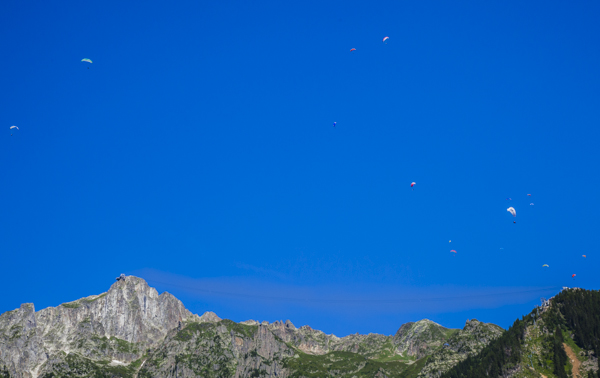 Paragliders pepper the sky, cable-car wires hardly be seen stretching from one mountain peak to the other.