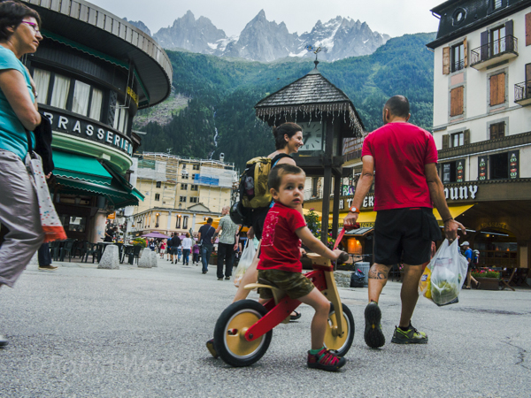Being pulled on a bicycle through the main square in Chamonix, mountain peaks projecting in the background.