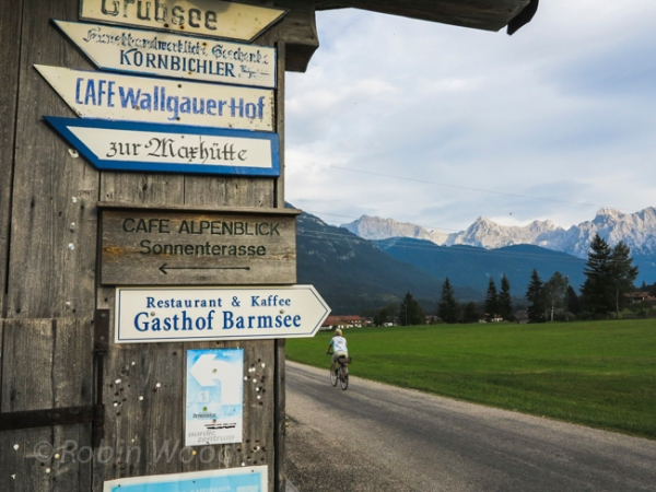 Faded German signs, a biker and mountain ranges.