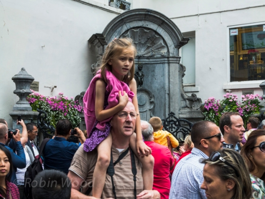 A small girl gets a shoulder ride past the small statue Manneken Pis.