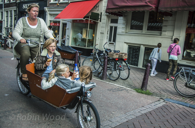 A determined mother shuttles children in a large basket on a bicycle.