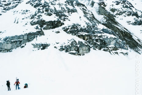 A large rock wall dwarfs skiers and illustrates the scale of Alaska's environment.