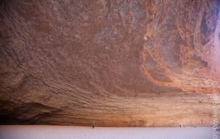 A person is dwarfed by Red Wall Cavern along the Colorado River.